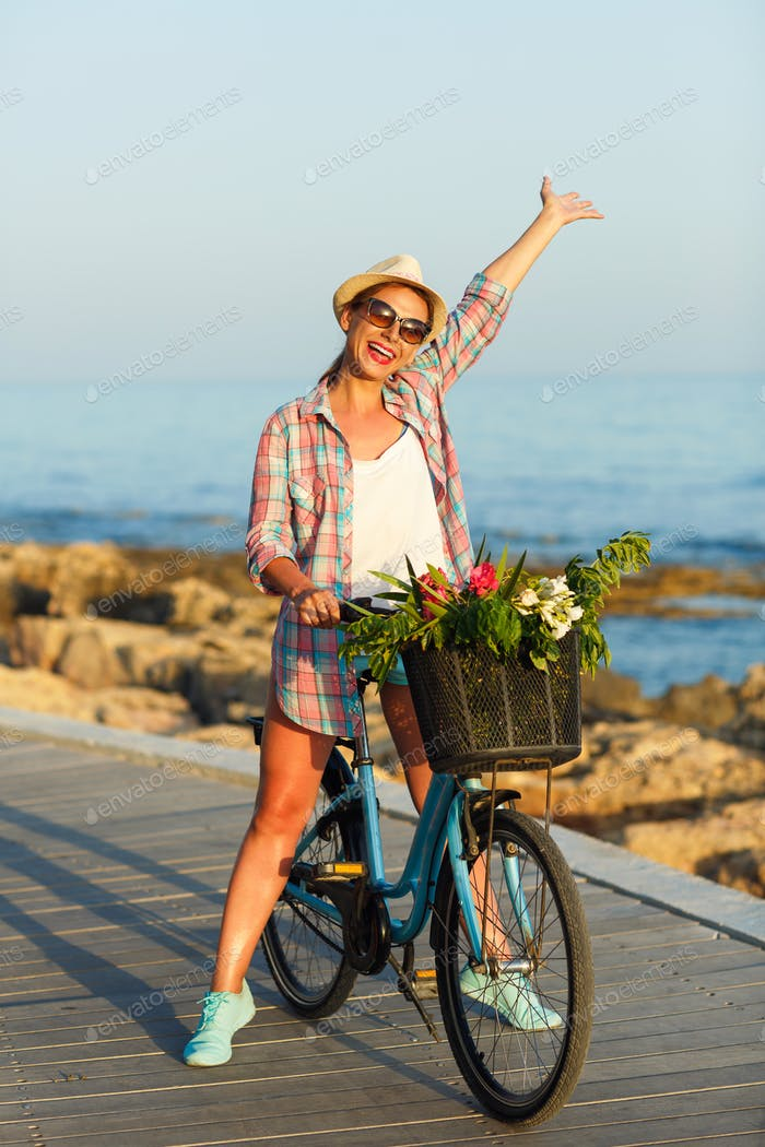 Carefree woman with bicycle riding on a wooden path at the sea,