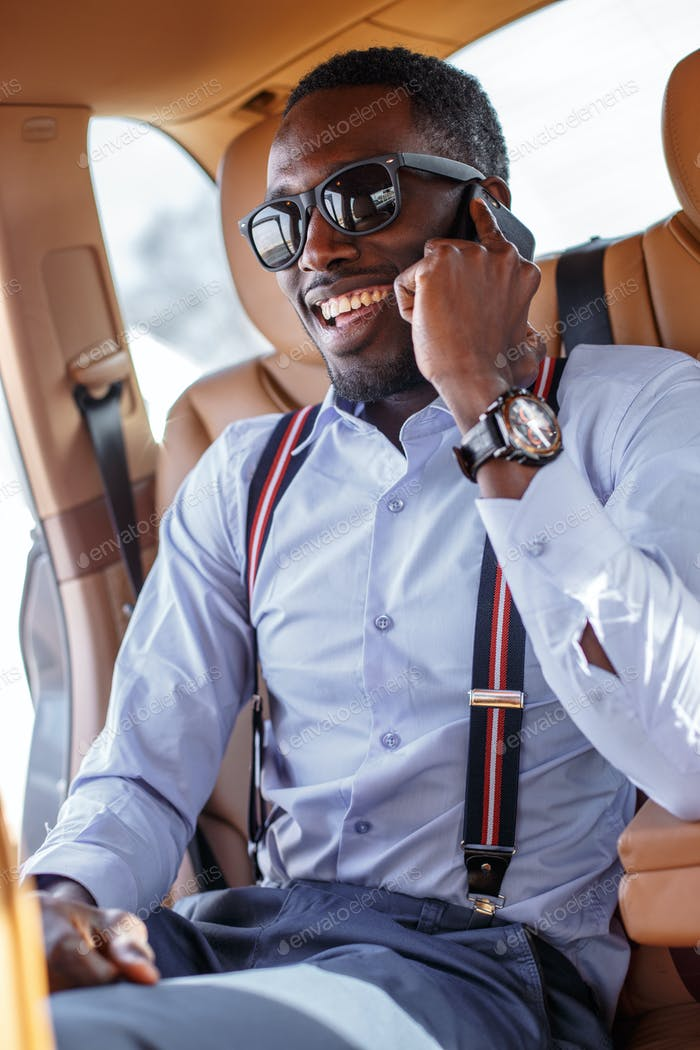African businessman  in the car speaking on smartphone.