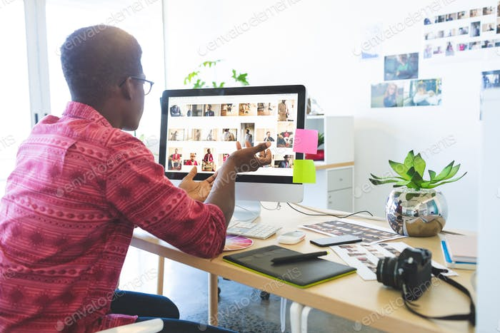 Rear view of young African-American graphic designer looking at computer in office