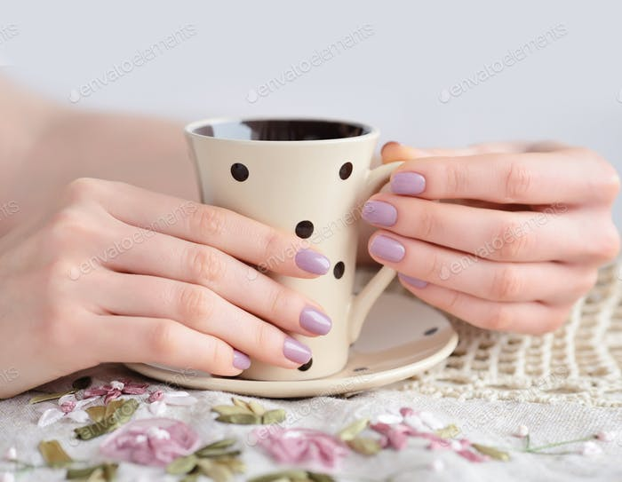 Cup of coffee in girl hands on linen tablecloth