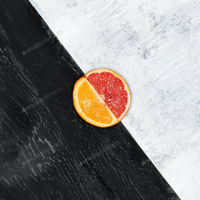 Grapefruit and orange citrus fruit halves on wooden