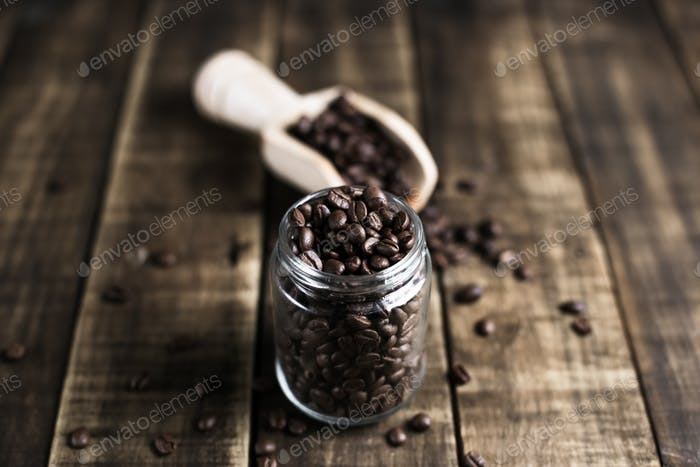coffee beans in a jug and wooden scoop
