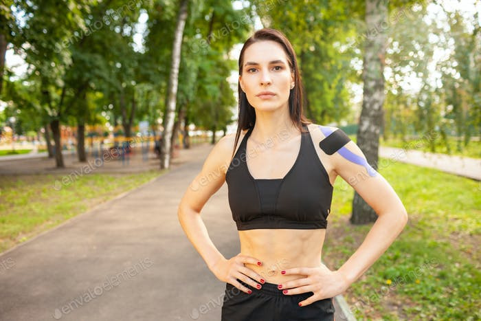 Fit woman with kinesiological taping posing outdoors