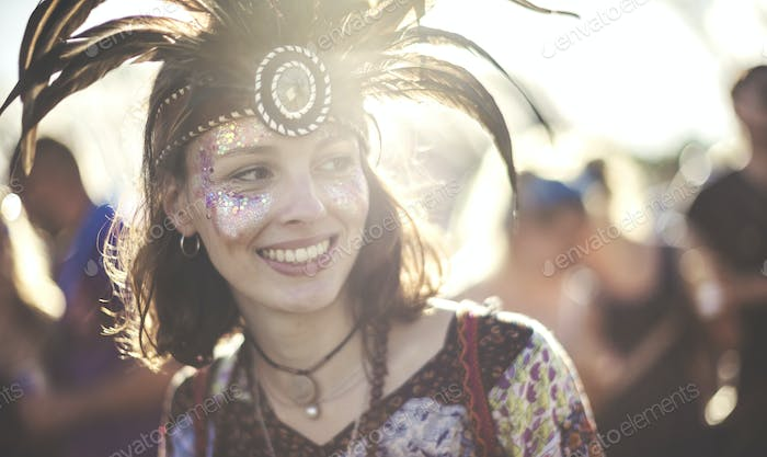 Young woman at a summer music festival wearing feather headdress and face painted, smiling.