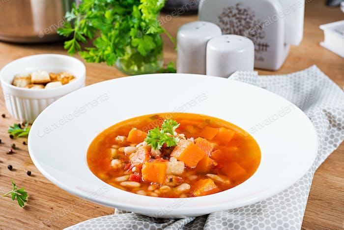 Томатный куриный суп с тыквой и белой фасолью в белой миске.