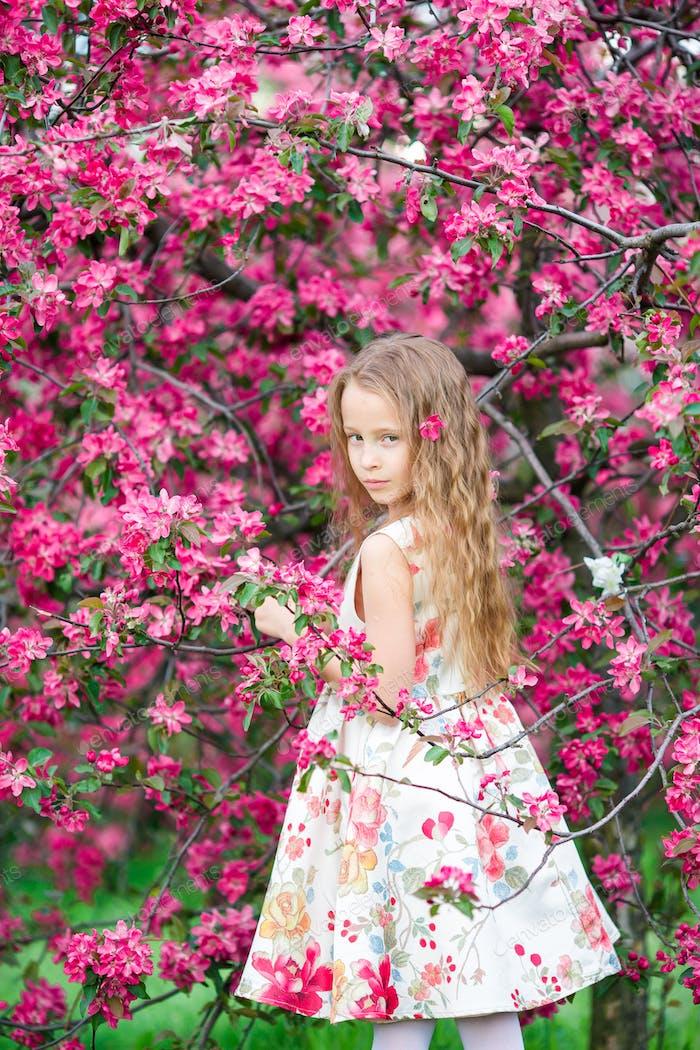 Kleines Mädchen im blühenden Apfelbaum Garten genießen Frühling
