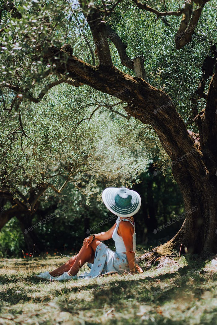 Beautiful elegant woman with straw hat sitting under an olive's tree