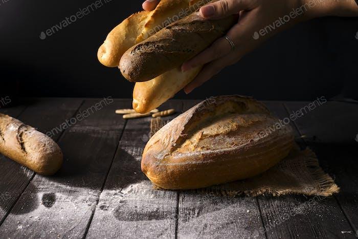 Close-up of woman hands take fresh bread. Dark photo