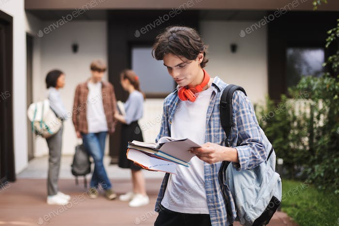 Young man with red headphones standing with backpack and reading book in courtyard of university