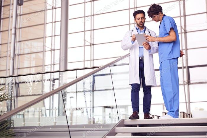 Zwei männliche Ärzte mit informellen Treffen in modernen Krankenhaus Blick auf digitale Tablet