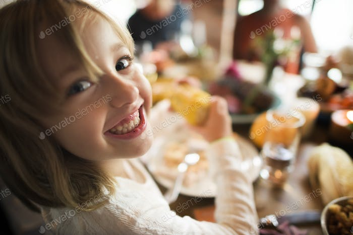 Little Girl Eating Corn Thanksgiving Celebration Concept