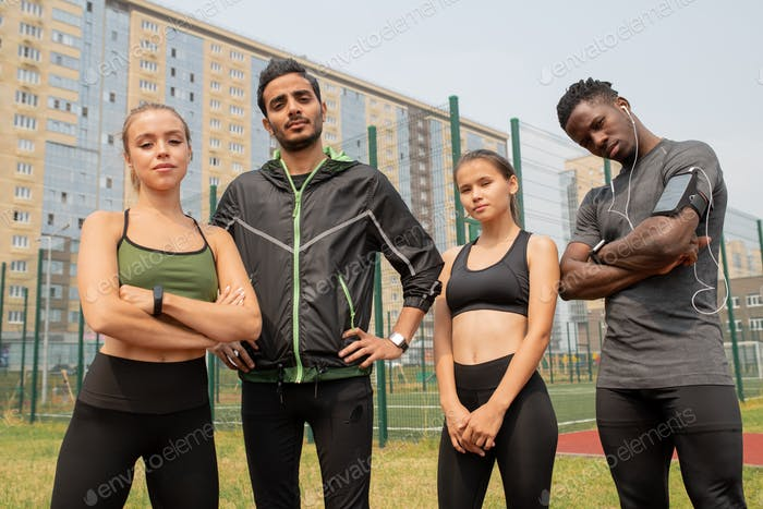 Young sporty men and women in activewear standing in urban environment
