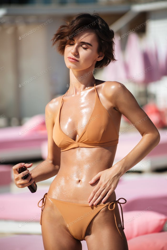 Beautiful lady in beige swimsuit smearing sun oil on her body for suntan