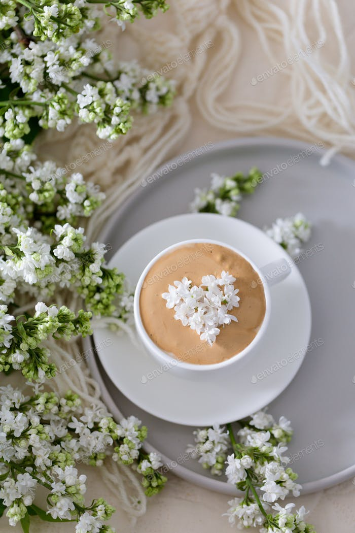 Composition with the branches of lilac and fresh coffee with foam in white cup