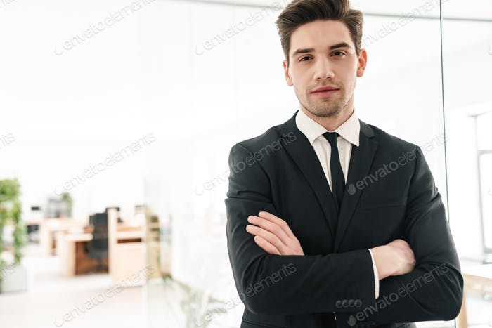 Image of serious young businessman wearing black suit standing with hands crossed