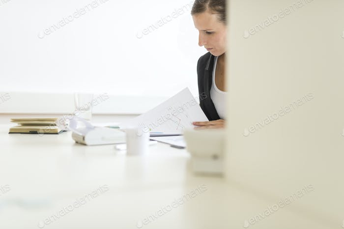 View around a partition of a woman in an office