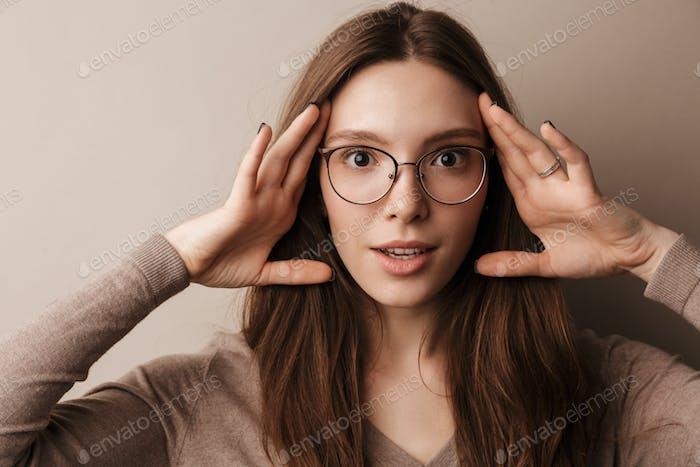Foto von jungen überraschten Frau packte ihren Kopf und Blick auf die Kamera
