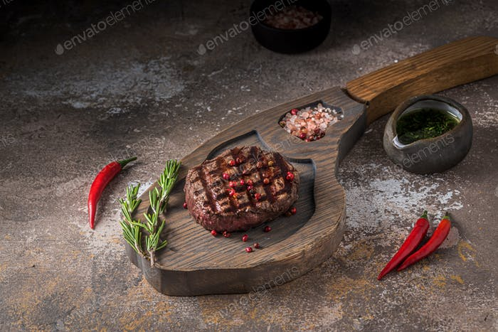 Fillet mignon steak on wooden board, copy space