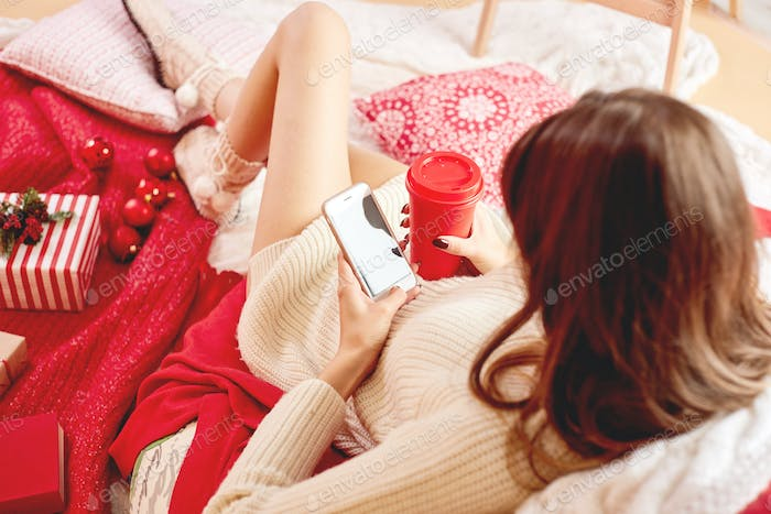 Girl dressed knitted dress and knitted socks lies on red-white blankets and pillows and holds a