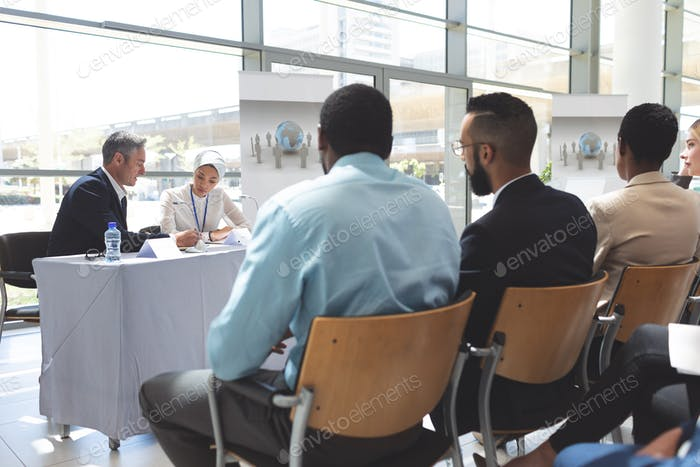 Rear view of diverse business people attending a business seminar in office building