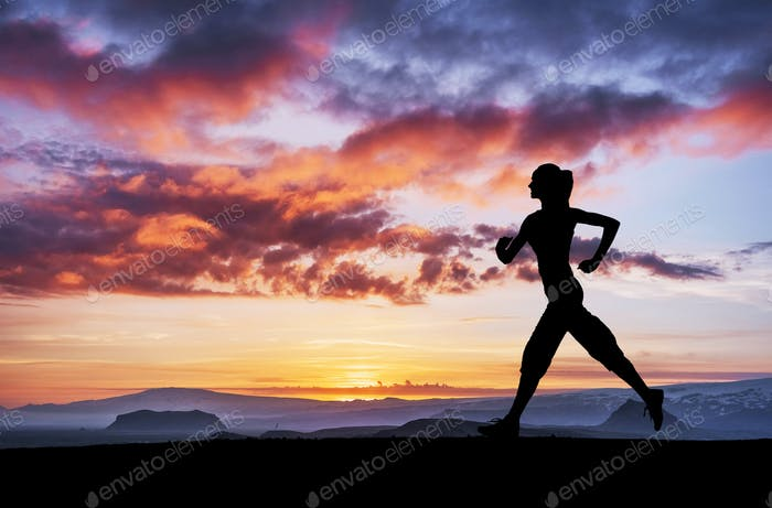 A sports girl at dawn is engaged in yoga. Fitness classes at sunset