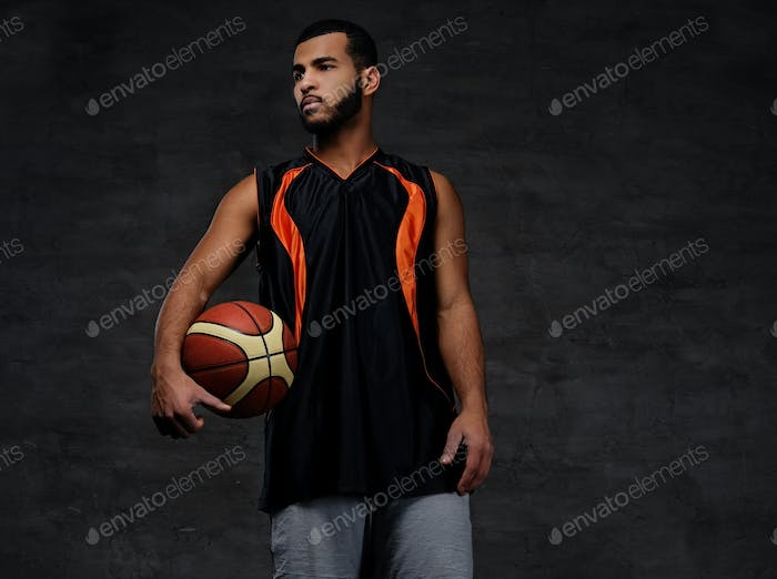 Young African-American basketball player in sportswear in a dark studio