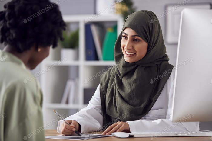 Female Doctor Or Consultant Wearing Headscarf Having Meeting With Female Patient To Discuss Scans