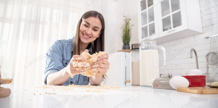 A young beautiful woman prepares homemade cakes in the kitchen.