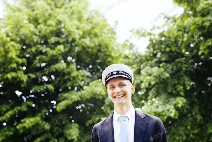 Portrait of happy male graduate against trees