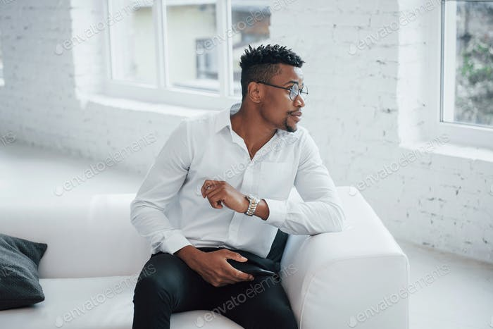 Stylish afro american guy in classic wear and glasses