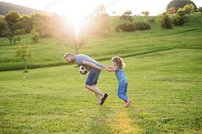 Father with a small daughter playing with a ball in spring nature at sunset.