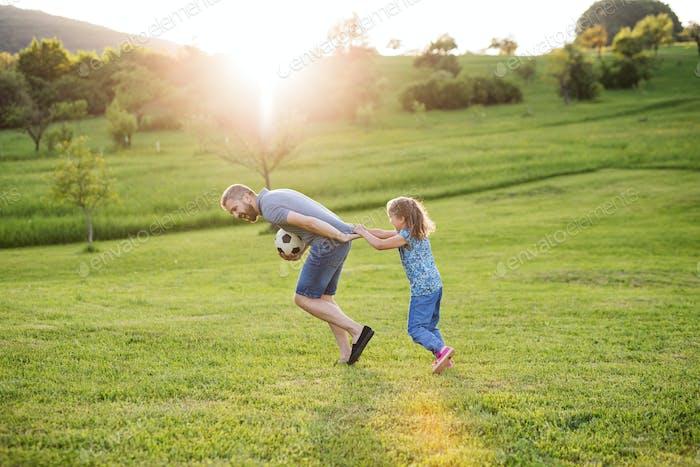 Vater mit einer kleinen Tochter spielen mit einem Ball im Frühling Natur bei Sonnenuntergang.