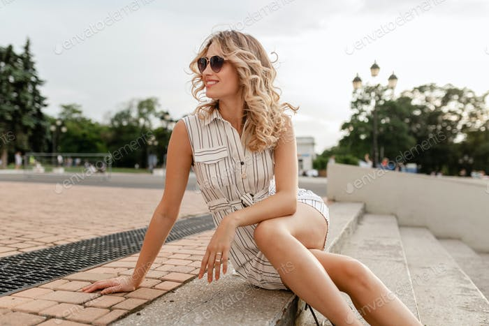 young attractive cute stylish blonde woman sitting in city street in summer fashion style