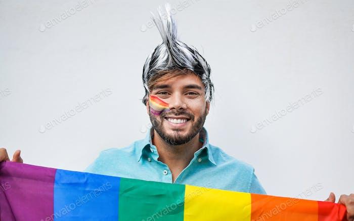 Young gay men with rainbow flag at pride parade