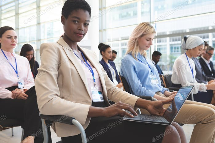Businesswoman with laptop looking at camera in seminar in a conference room
