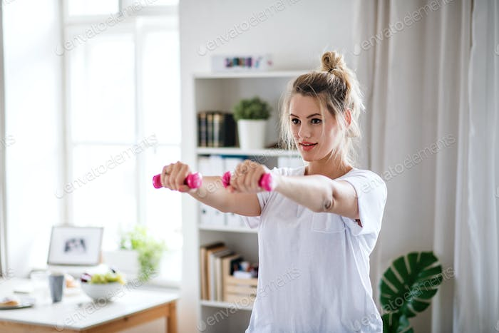 Young woman with dumbbells doing exercise in bedroom indoors at home.