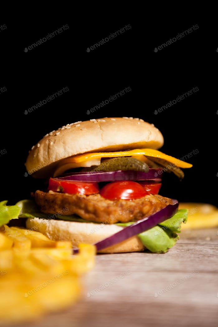 Classic cheeseburgers on wooden plate