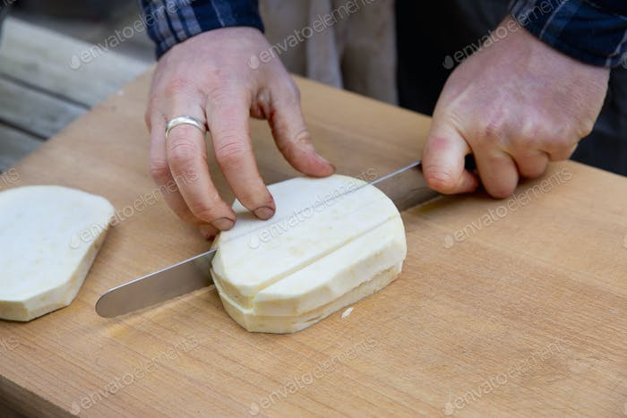 A man with a long knife chopping celeriac into cubes on a chopping board.
