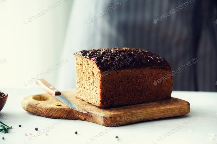 Woman hands slicing freshly backed bread. Handmade brown loaf of bread, bakery concept, homemade
