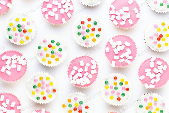 Multiple colorful nicely decorated muffins on a white background.