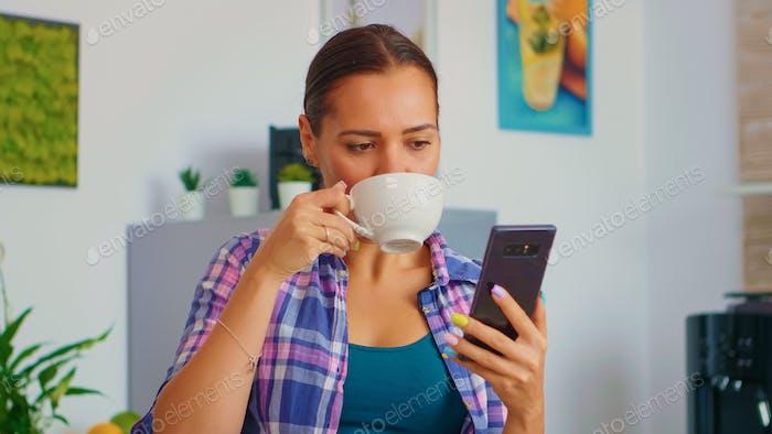 Женщина прокрутка и пьет чай