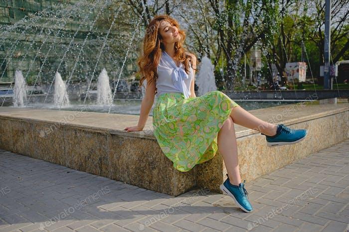 Beautiful girl sitting near fountain
