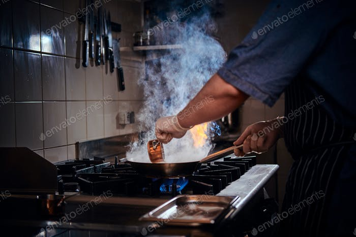 Chef mixing and frying flambe on a pan with steam in a restaurant kitchen