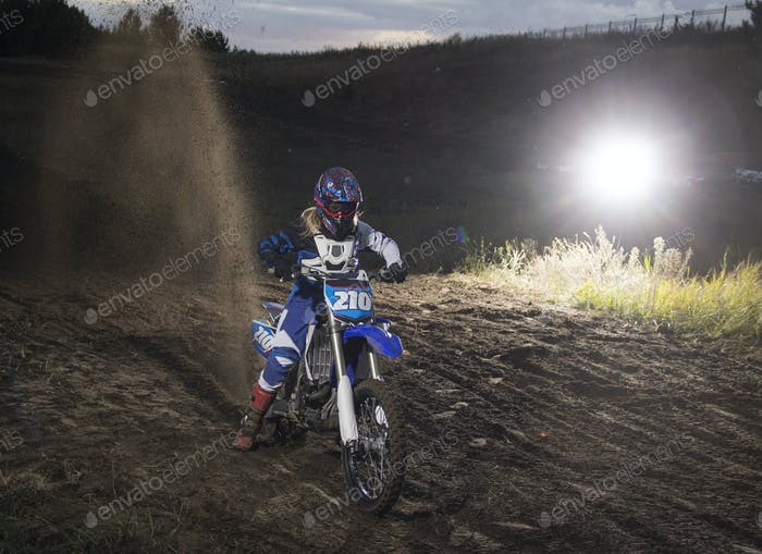 Motocross rider creates a  cloud of dust and debris