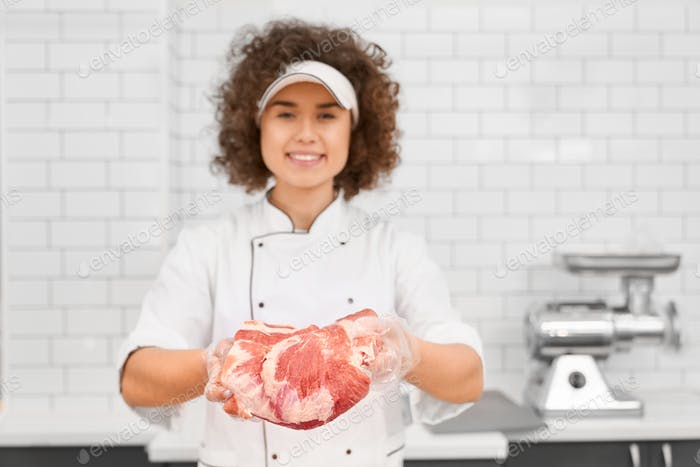 Female butcher demonstrating meat in supermarket