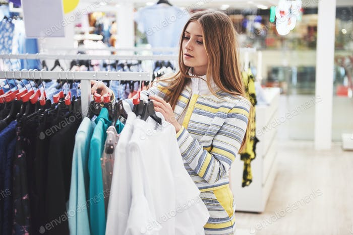 Woman shopping clothes. Shopper looking at clothing indoors in store. Beautiful happy smiling asian