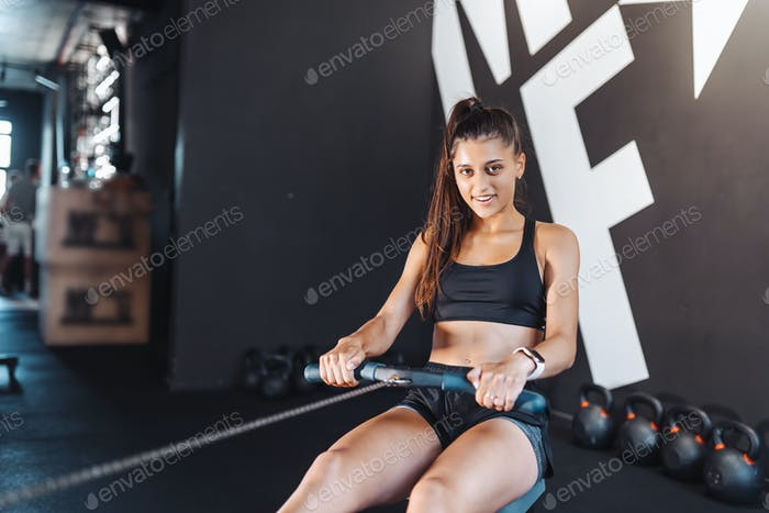 Young woman training and pulling weights in seated cable row machine