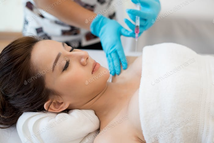 Surgery cosmetology inject botox in breast.