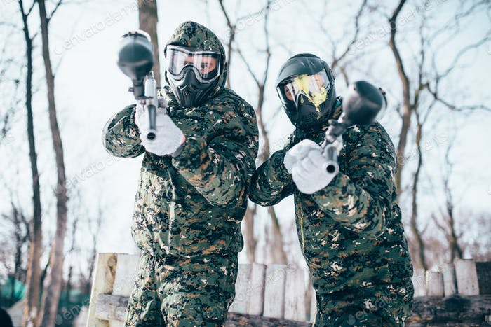 Paintball players in splattered masks after battle