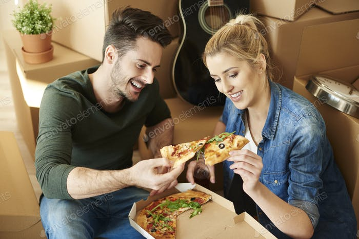 Couple eating pizza next to moving boxes